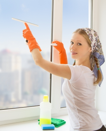 beautiful young housewife washing the window photo