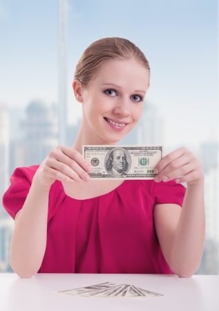 young woman businesswoman sitting at the table with money, dollars photo