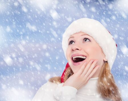 happy surprised funny girl in a Christmas hat on winter background with snow photo