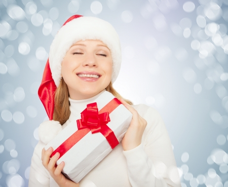 closed ribbon: Young beautiful woman with eyes closed in a Christmas hat with a gift with a red ribbon