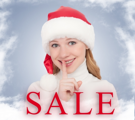 Christmas Sale and happy young woman in a Santa hat photo