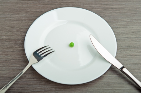 diet concept. one pea on an empty white plate with knife and fork photo