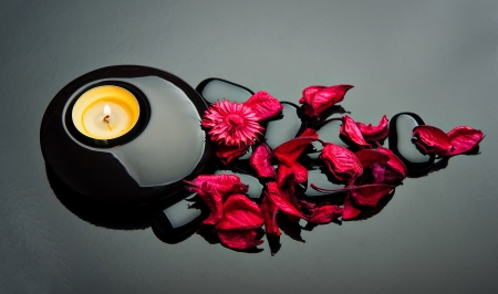 spa background. red petals and stones black with candle photo