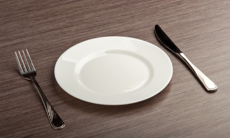 table setting. empty white plate with knife and fork