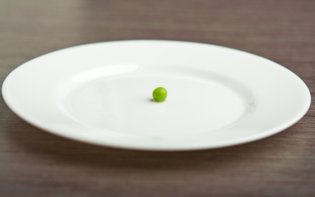 empty plate: diet concept. one green pea on an empty white plate