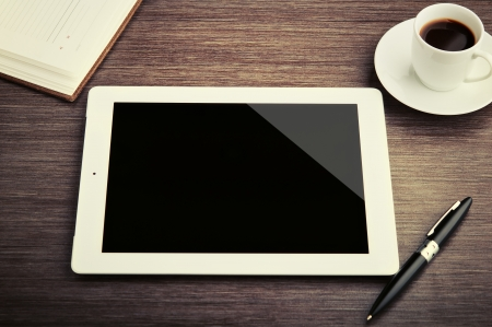 paper screens: empty tablet and a cup of coffee on the desk