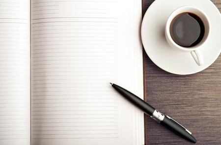 pluma y papel: Abra un cuaderno en blanco blanco, pluma y taza de caf� sobre la mesa Foto de archivo