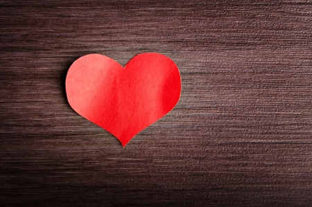 background in the style of Valentine's Day. red heart on a wooden background photo