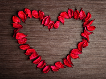 background in the style of Valentines Day. petals of red roses in the shape of a heart on a wooden background photo