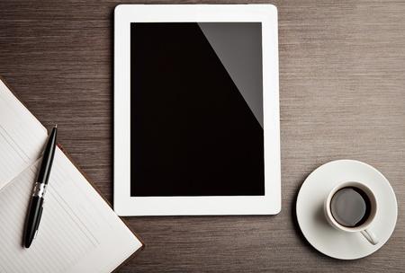 monitor de computadora: tableta vac�a y una taza de caf� sobre la mesa