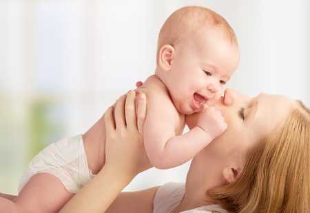 madre y bebe: Familia feliz. joven madre besando a un bebé Foto de archivo