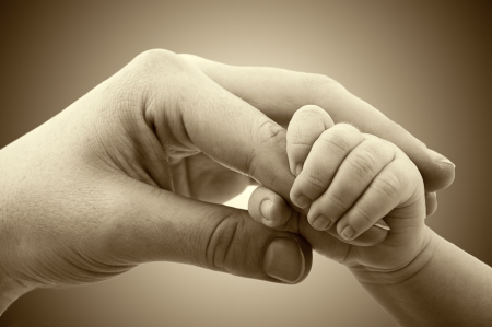 mother: concept of love and family. hands of mother and baby closeup Stock Photo