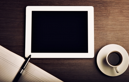 empty tablet pc and a coffee and notebook with pen on the office desk Stock Photo