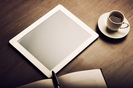 paper screens: empty tablet pc and a coffee and notebook with pen on the office desk Stock Photo