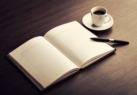 escribiendo: Abra un cuaderno en blanco blanco, pluma y taza de caf� sobre la mesa Foto de archivo