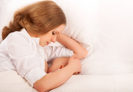 feeding baby: mother feeding breast her baby in the bed. sleeping together