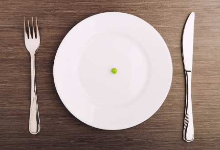 diet concept. one pea on an empty white plate with knife and fork Stock Photo