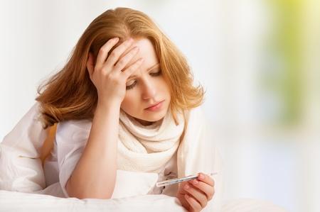 epuise: Femme avec thermom�tre malade rhume, la grippe, la fi�vre et la migraine au lit Banque d'images