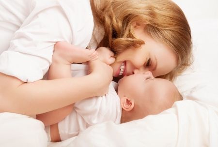family tickle: happy family. baby and mother play, kiss, tickle, laugh in white bed