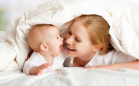 madre y bebe: familia feliz. Madre y bebé jugando y sonriendo bajo una manta