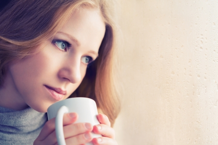 beautiful dreamy girl with a cup of hot drink coffee at the window