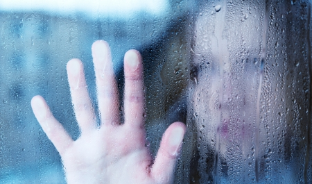 hand of young  woman  melancholy and sad  at the window in the rain photo