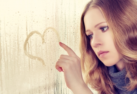 sad enamored girl draws a heart on the window in the rain photo