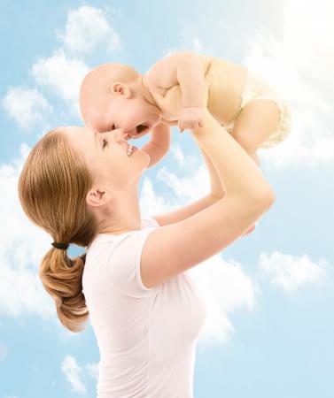 parentalidade: fam�lia feliz. M�e joga-se e beija o beb� no c�u na natureza