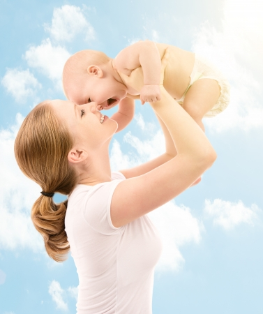 happy family. Mother throws up and kissing baby in the sky in nature Stock Photo