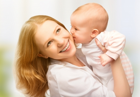 Happy cheerful family. Mother and baby kissing, laughing and hugging photo