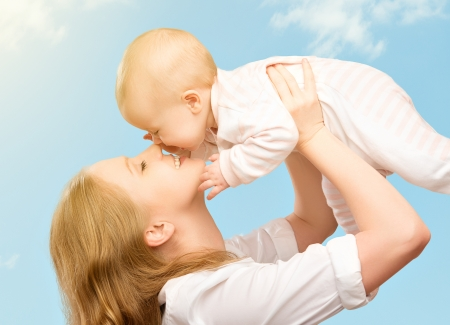 mom baby: happy family. Mother throws up and kissing baby in the sky in nature Stock Photo