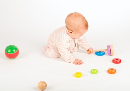 Happy baby playing with a toy pyramid on white background photo