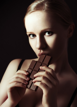 sexy beautiful young woman eating chocolate on a dark background photo