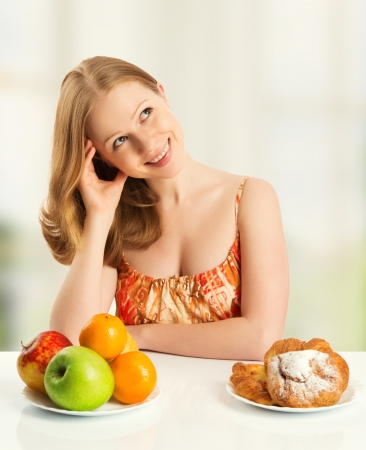 woman with a buns and fruits choose between healthy and unhealthy food photo