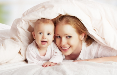 blankets: happy family. Mother and baby playing and smiling under a blanket  Stock Photo