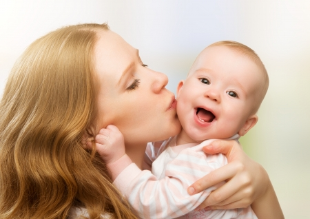 mum and baby: Happy cheerful family. Mother and baby kissing, laughing and hugging Stock Photo