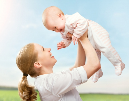 babies laughing: happy family. Mother throws up  baby in the sky in nature Stock Photo