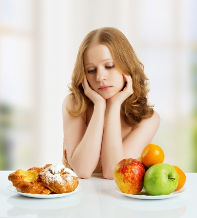 health choice: woman with a buns and fruits choose between healthy and unhealthy food