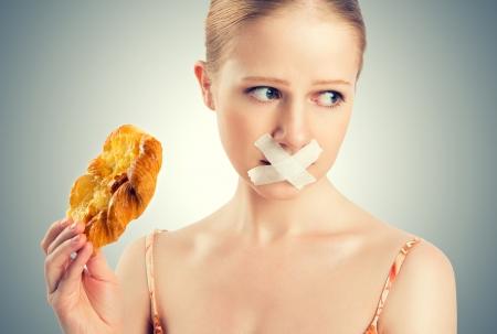 concept de régime. femme bouche scellée avec conduit rêver bande de biscuits et brioches.