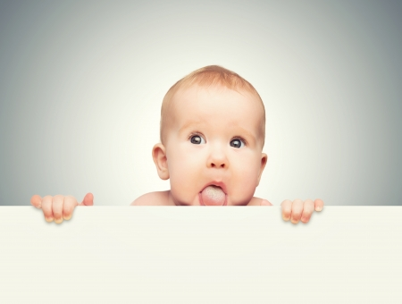 blank card: funny cute baby with white blank banner in hand isolated on a gray background
