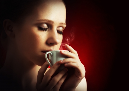 portrait of sexy woman enjoying a hot cup of coffee on a dark background photo