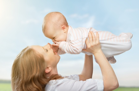 mum and baby: happy family. Mother throws up  baby in the sky in nature Stock Photo