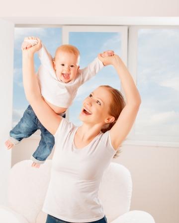 playing with baby: Madre e bambino stanno giocando giochi attivi, fanno ginnastica e ridendo in casa contro la finestra e il cielo