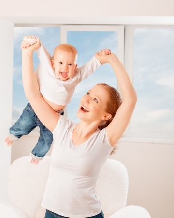 Mother and baby are playing active games, do gymnastics and laughing at home against the window and the sky photo