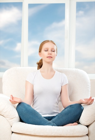 rest in peace: woman meditating, relaxing, sitting in a lotus position on the sofa at home, against the window and the sky