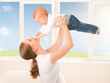 throws: happy family. Mother throws up  baby, playing at home Stock Photo
