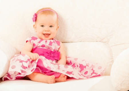 Beautiful pretty little baby girl in a pink dress sitting on the couch at home and smiling photo