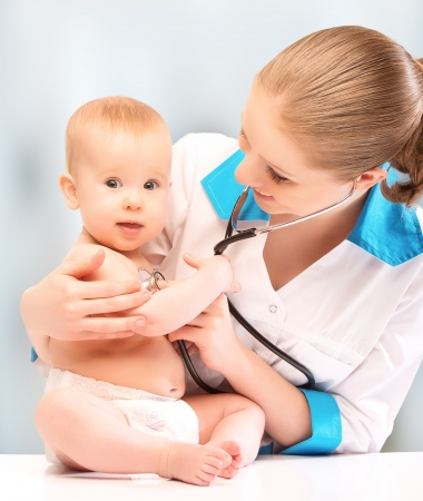 baby sick: baby at the doctor pediatrician. doctor listens to the heart with a stethoscope