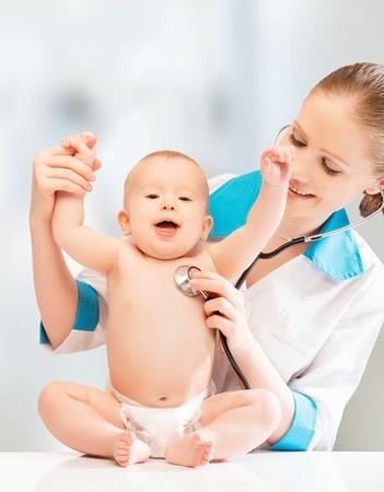 pediatra: Beb� engra�ado feliz no m�dico pediatra. m�dico escuta o cora��o com um estetosc�pio