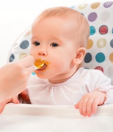 feeding baby: Mom feeds funny baby from a spoon Stock Photo